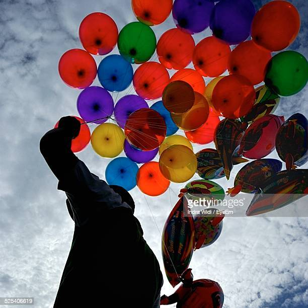 Low Angle View Of Balloon Seller Against Cloudy Sky