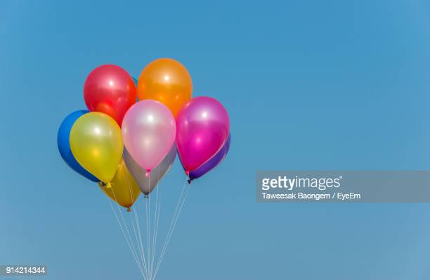low angle view of balloons against blue sky - helium balloon stock pictures, royalty-free photos & images