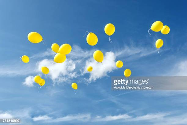 low angle view of balloons against sky - luftballons himmel stock-fotos und bilder