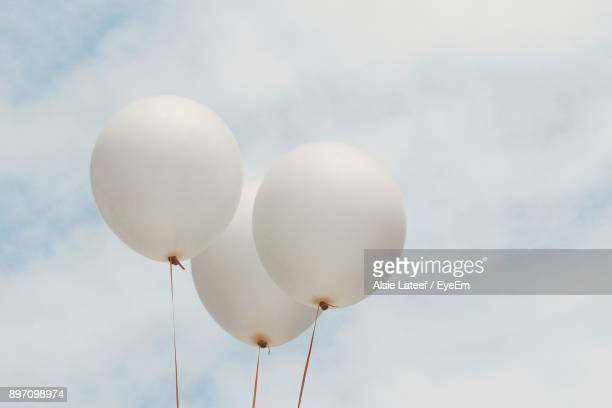 low angle view of balloons against sky - helium balloon stock pictures, royalty-free photos & images