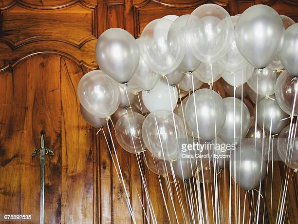 Low Angle View Of Balloons Against Wooden Wall