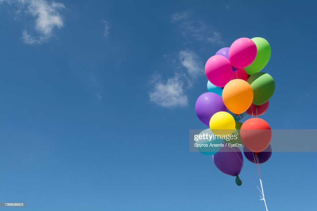 Low Angle View Of Balloons Flying Against Blue Sky : Stock Photo