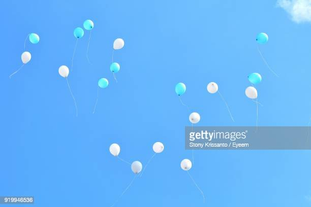 low angle view of balloons flying against blue sky - luftballons himmel stock-fotos und bilder