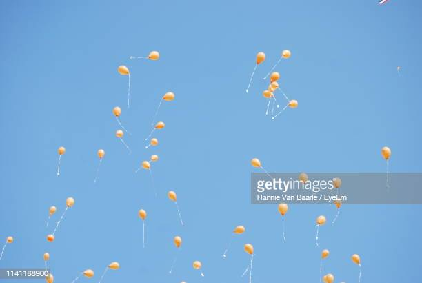 Low Angle View Of Balloons Flying Against Clear Blue Sky During Sunny Day