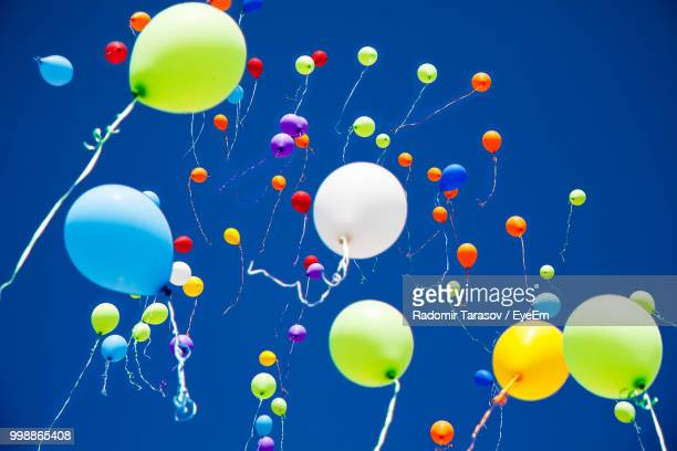 low angle view of balloons flying against clear blue sky during sunny day - luftballons himmel stock-fotos und bilder