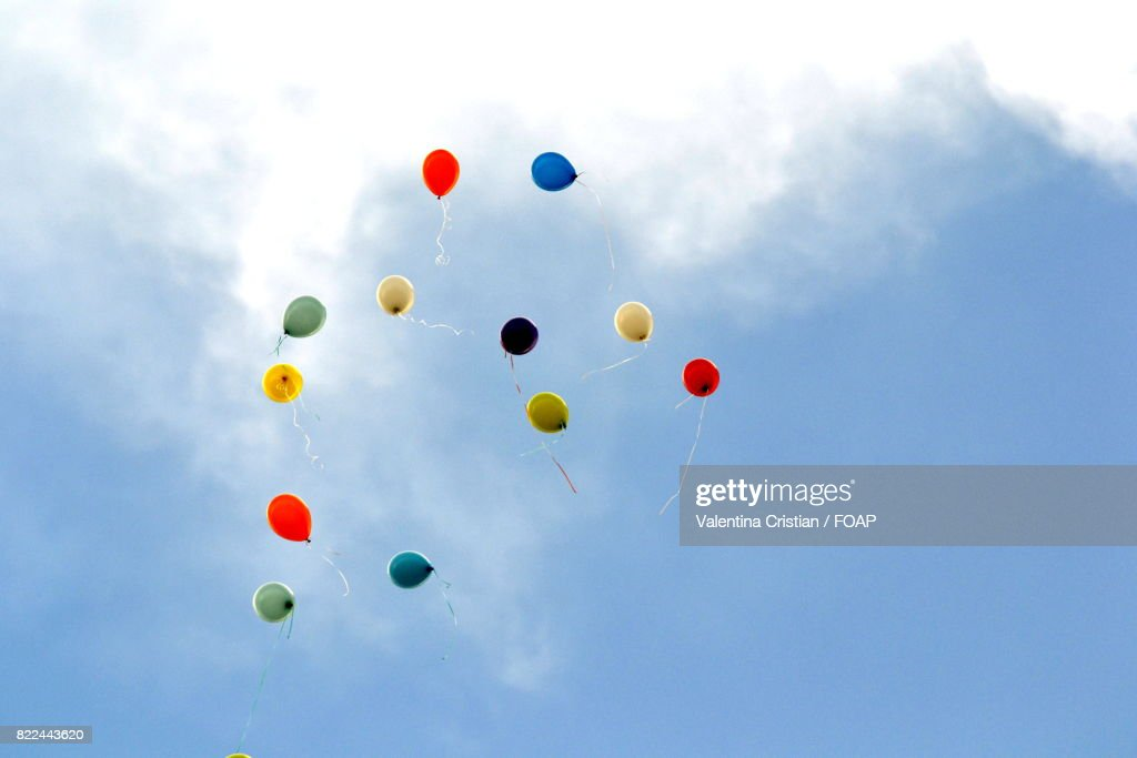 Low angle view of balloons flying in air : Stock Photo