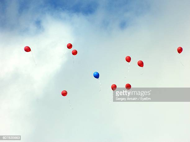 Low Angle View Of Balloons Flying In Cloudy Sky