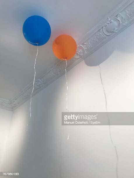 low angle view of balloons hanging from ceiling - helium balloon stock pictures, royalty-free photos & images