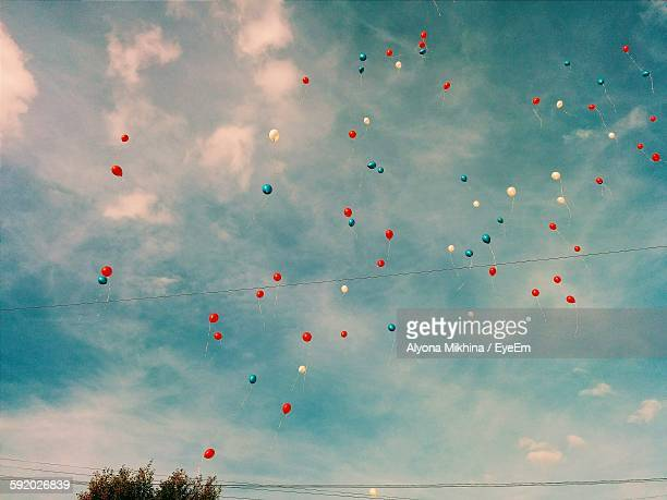 low angle view of balloons in sky - luftballons himmel stock-fotos und bilder