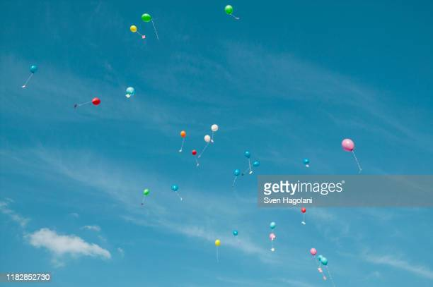 low angle view of balloons with messages in mid-air against sky - luftballons himmel stock-fotos und bilder
