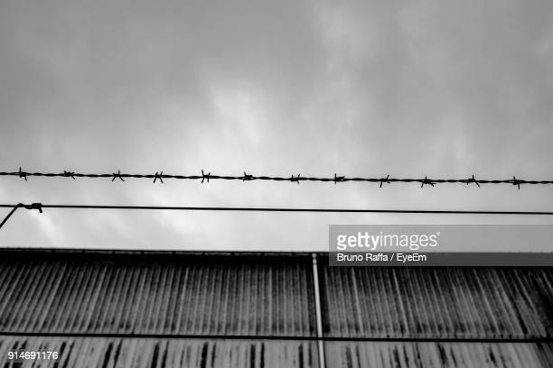 low angle view of barbed wire against cloudy sky - barbed wire stock pictures, royalty-free photos & images