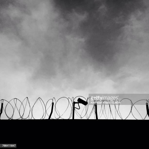 low angle view of barbed wire against sky - barbed wire stock pictures, royalty-free photos & images