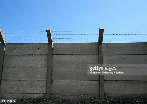 Low Angle View Of Barbed Wire On Fence Against Blue Sky