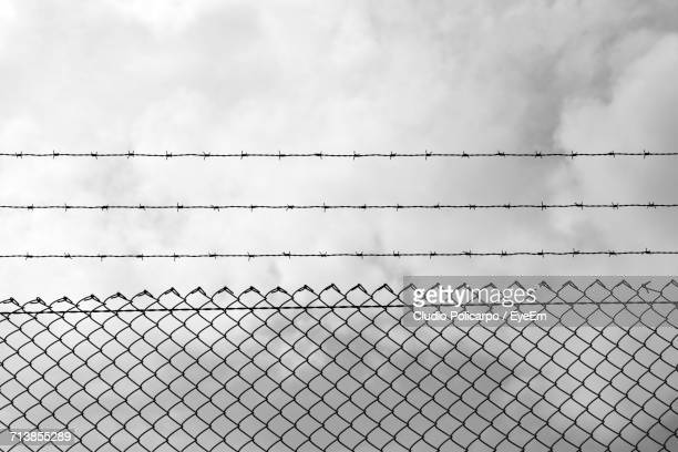 low angle view of barbed wire over chainlink fence against cloudy sky - barbed wire stock pictures, royalty-free photos & images