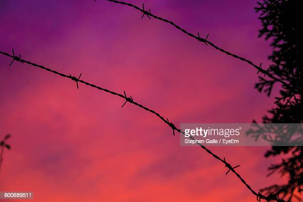 Low Angle View Of Barbed Wires Against Orange Sky