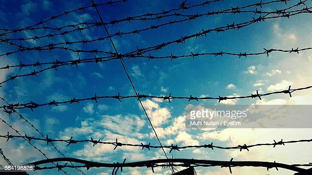 Low Angle View Of Barbed Wires Fence Against Sky
