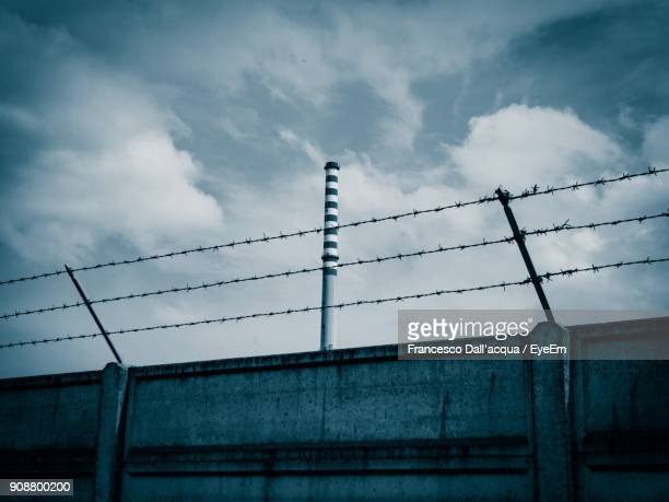 low angle view of barbed wires on wall against cloudy sky - barbed wire stock pictures, royalty-free photos & images