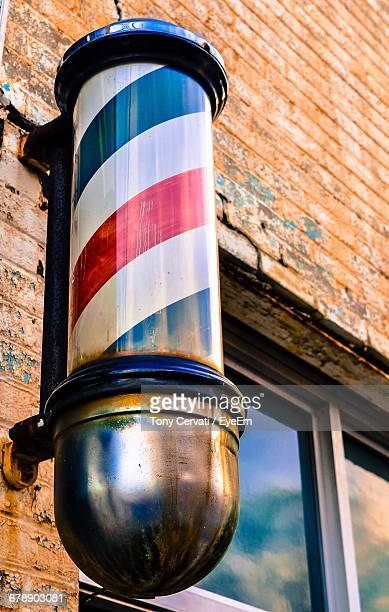 Low Angle View Of Barber Shop Pole On Old Building