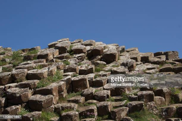 low angle view of basalt against clear blue sky - stone material stock pictures, royalty-free photos & images