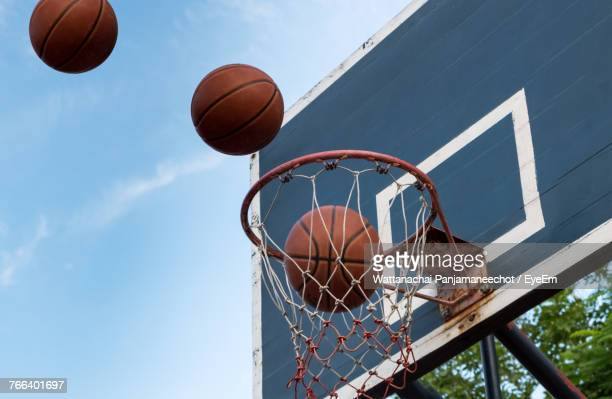 low angle view of basketball hoop against sky - making a basket scoring stock photos and pictures