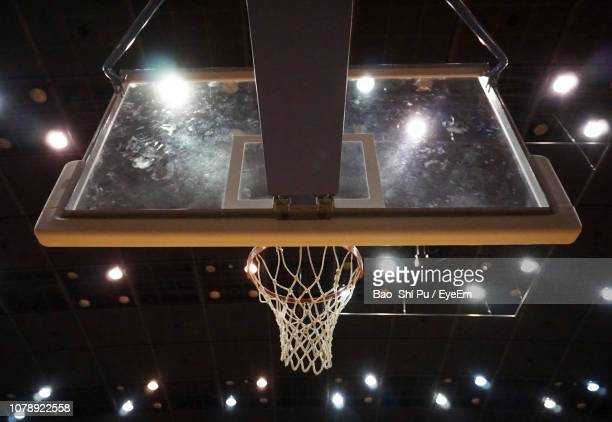 low angle view of basketball hoop at illuminated stadium - basketball stadium stock pictures, royalty-free photos & images
