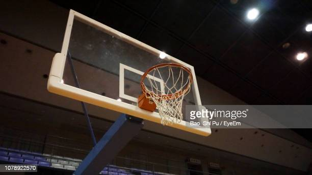 low angle view of basketball hoop at illuminated stadium - basketball hoop stock pictures, royalty-free photos & images