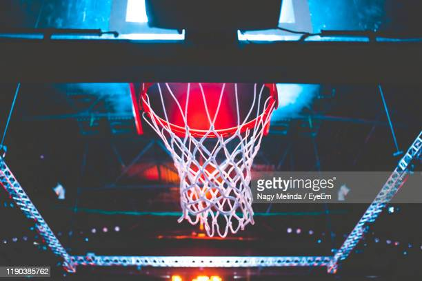 low angle view of basketball hoop at night - baloncesto fotografías e imágenes de stock