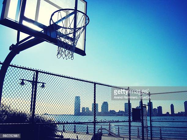 Low Angle View Of Basketball Hoop By River Against Clear Blue Sky