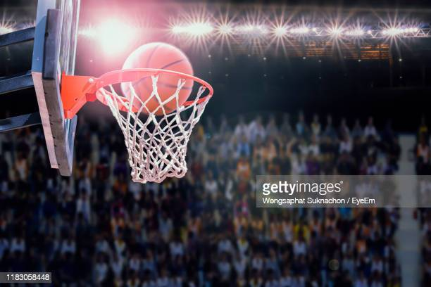 low angle view of basketball in hoop - basketball stadium stock pictures, royalty-free photos & images
