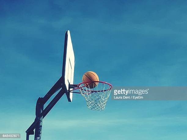 low angle view of basketball on hoop against sky - basketball hoop stock pictures, royalty-free photos & images