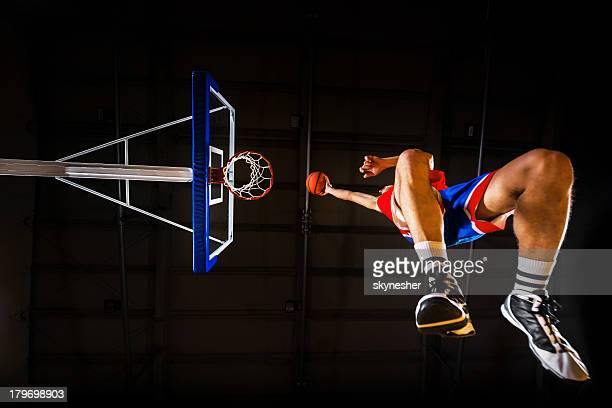 Low angle view of basketball player slam dunking the ball.