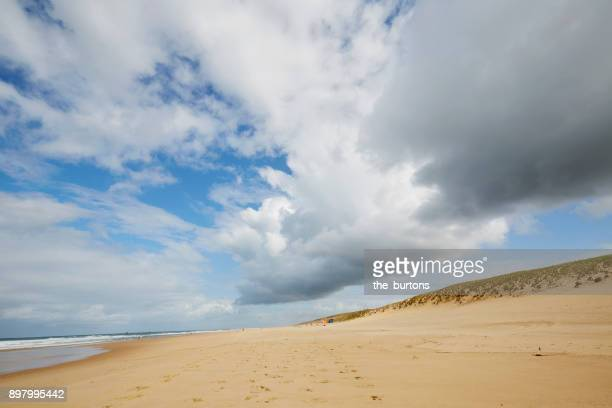 low angle view of beach, dunes and cloudy sky - cap ferret photos et images de collection