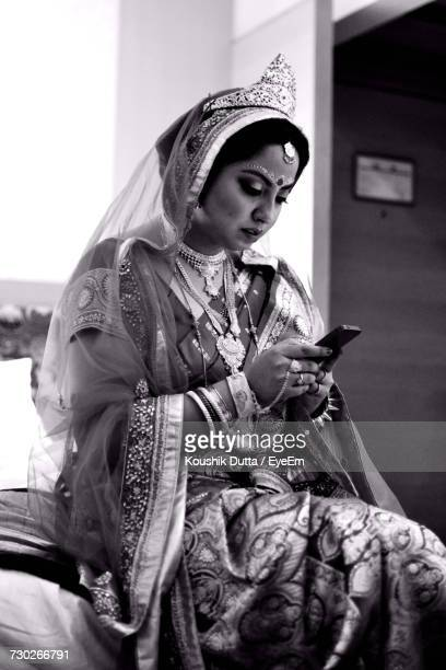 Low Angle View Of Beautiful Bride Using Mobile Phone While Sitting On Bed At Home