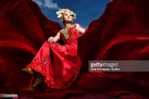 Low Angle View Of Beautiful Model Wearing Red Period Costume While Sitting Amidst Curtain