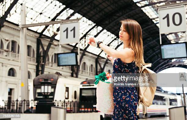 Low Angle View Of Beautiful Woman Checking Time At Railroad Station