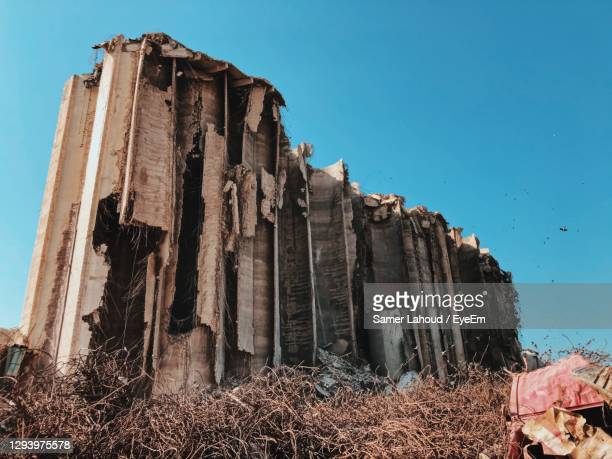 low angle view of beirut explosion damaged building against clear blue sky - beirut stock pictures, royalty-free photos & images