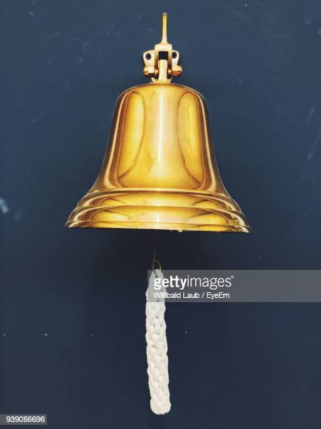 low angle view of bell hanging against wall - campana fotografías e imágenes de stock