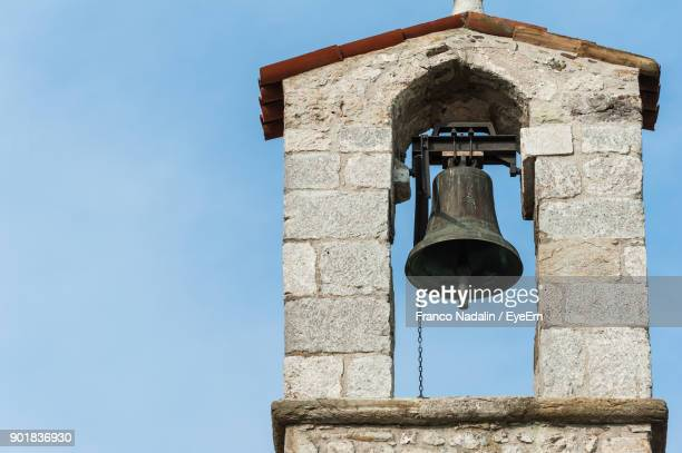 low angle view of bell tower against blue sky - campana fotografías e imágenes de stock