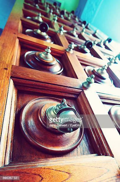 Low Angle View Of Bells Mounted On Wooden Temple Door