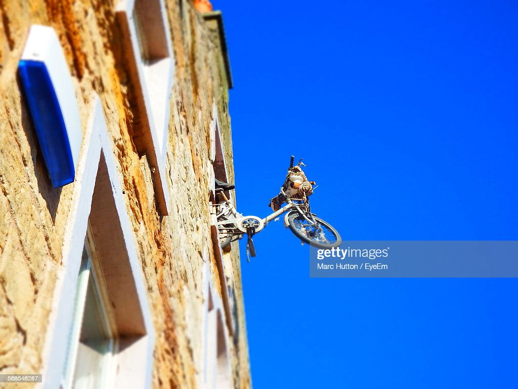 Low Angle View Of Bicycle Hanging Out Of Window Against Clear Blue Sky : Stock Photo