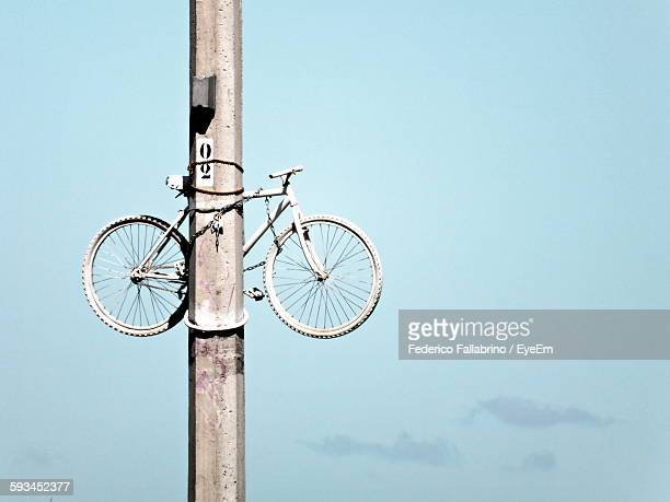 Low Angle View Of Bicycle Locked On Pole Against Sky