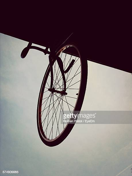 low angle view of bicycle on roof against sky at dusk - roman pretot fotografías e imágenes de stock