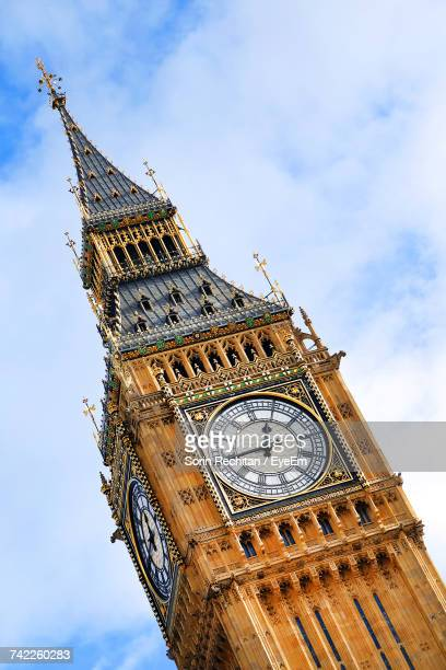 low angle view of big ben against cloudy sky - big ben stockfoto's en -beelden