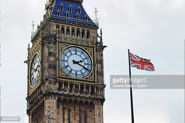 Low Angle View Of Big Ben And British Flag Against Clear Sky