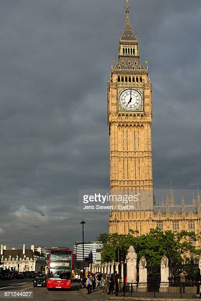 Low Angle View Of Big Ben By Street Against Cloudy Sky