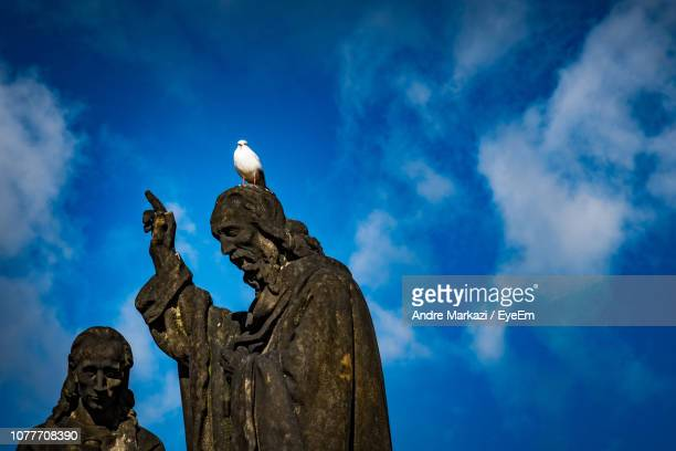 Low Angle View Of Bird On Statue Against Blue Sky