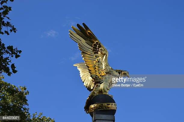 Low Angle View Of Bird Statue Against Clear Blue Sky