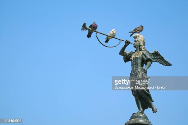 low angle view of birds perching on statue against clear blue sky - lima animal stock pictures, royalty-free photos & images