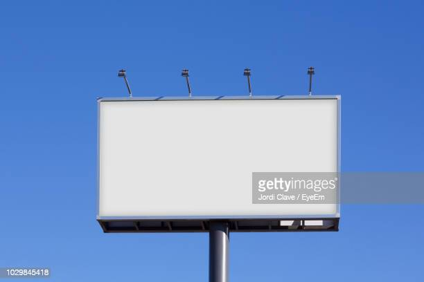 low angle view of blank billboard against clear blue sky - billboard stock pictures, royalty-free photos & images