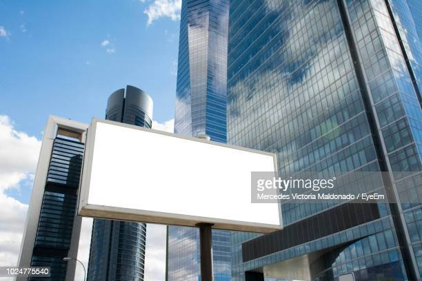 low angle view of blank billboard against modern buildings in city - tabellone foto e immagini stock